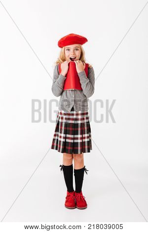Full length portrait of an astonished little schoolgirl dressed in uniform with backpack holding book and looking at camera isolated over white background