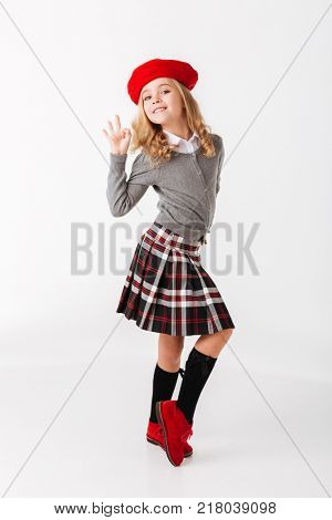 Full length portrait of a cute little schoolgirl dressed in uniform standing and showing ok gesture isolated over white background