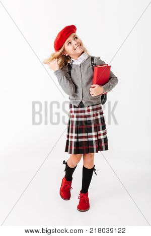 Full length portrait of a lovely little schoolgirl dressed in uniform with backpack holding book and looking up at copy space isolated over white background