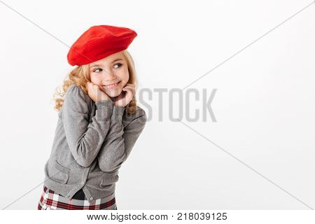 Portrait of a smiling little schoolgirl dressed in uniform looking away at copy space isolated over white background