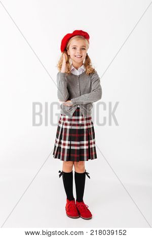 Full length portrait of a smiling little schoolgirl dressed in uniform standing and holding hand for an answer isolated over white background