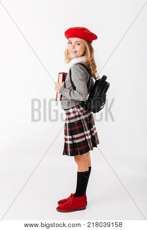 Full length portrait of a happy little schoolgirl dressed in uniform with backpack holding book and looking at camera isolated over white background