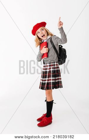 Full length portrait of a cheery little schoolgirl dressed in uniform with backpack holding book and pointing finger up at copy space isolated over white background