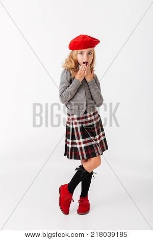 Full length portrait of a lovely little schoolgirl dressed in uniform standing and covering her mouth with palm isolated over white background