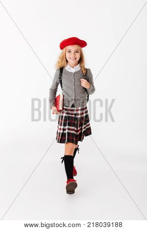 Full length portrait of a happy little schoolgirl dressed in uniform with backpack holding book while walking and looking at camera isolated over white background