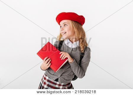 Close up portrait of a cute little schoolgirl dressed in uniform holding book and looking away at copyspace isolated over white background