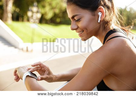 Close up of a happy fitness woman leaning on a rail and checking her smart watch outdoors