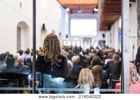 Speaker Giving a Talk at Business Meeting. Audience in the conference hall. Business and Entrepreneurship. Shot trough glass. Focus on unrecognizable woman in the audience.
