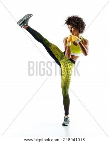 Girl practicing tae-bo exercises kicking forward with legs. Photo of sporty african girl wearing sports clothes over white background
