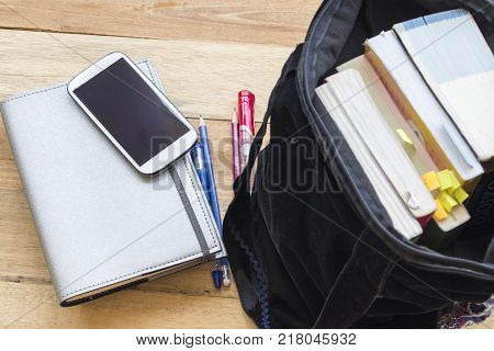 all book in bag with notebook memo for study on table