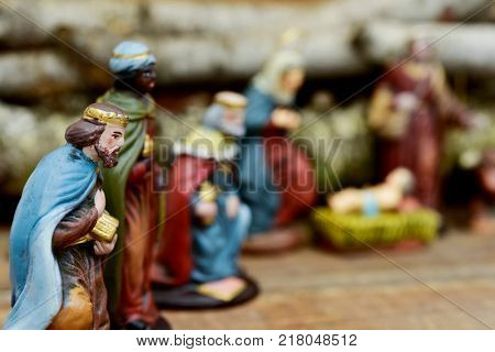 closeup of the three kings carrying their gifts adoring the Child Jesus on a rustic nativity scene