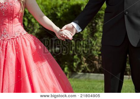 Close cropped outdoor photo of couple dressed in formal wear holding hands