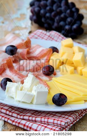 Snack cheese plate with grapes  and smoked bacon