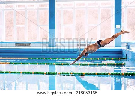 Senior man in an indoor swimming pool. Active pensioner enjoying sport. An old man jumping in the pool.
