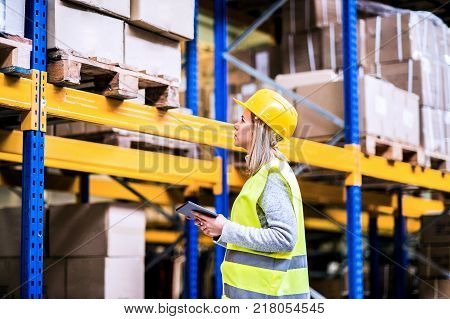 Young woman warehouse worker with tablet. A supervisor controlling stock. poster