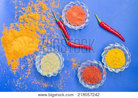 Colorful Spices And Herbs In Glass Dishes On A Blue Background. Top View.