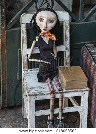 Wooden Worn-out Woman Marionette on White Chair.