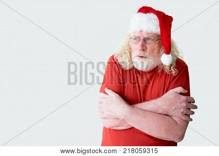 Santa Claus in t-shirt shivering with cold. Portrait of freezing old man. Aged Santa Claus feeling cold
