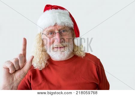 Studio shot of senior man in Christmas hat. Aged positive man raising finger and looking at camera. Portrait of old man in Santa Claus hat