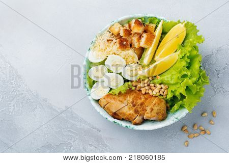 Traditional Caesar Salad with quail eggs and pine nuts in a light ceramic bowl on dark stone or concrete background. Selective focus. Top view.