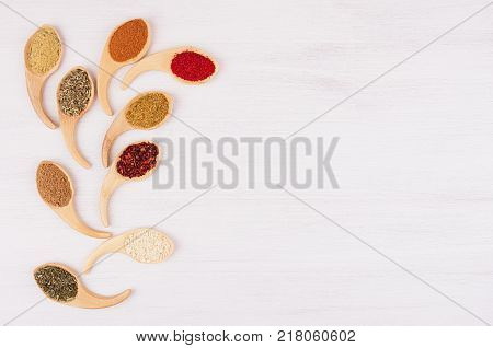 Assortment colorful powdered spices in bamboo spoons as decorative quaint branch. White wood background top view copy space.
