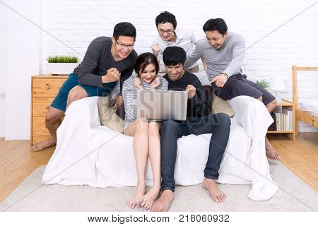 Group of five young asian people watching something with laptop and celebrate together at sofa in home or room. Happy and cheerful with friends in casual style. Funny and cheerful activity concpet.