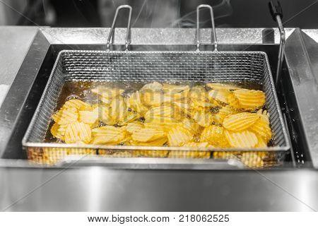 Potato chip deep frying in hot oil in Deep Fryer