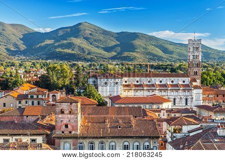 Vivid rooftops of city Lucca with background of colorful green mountains range Italy.