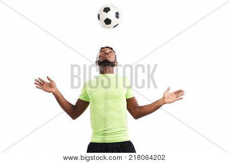 Waist-up portrait of bearded Nigerian soccer player juggling ball on his head while standing against white background