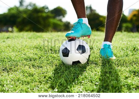 Close-up shot of unrecognizable professional soccer player wearing football boots standing at sunny field with one foot on ball