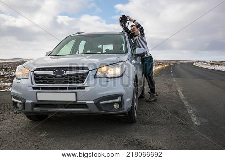 Gray car with driver on the roadway on the background of the partially snow fields and cloudy sky in Iceland. Man with a camera preparing to shooting outside the car. Horizontal.