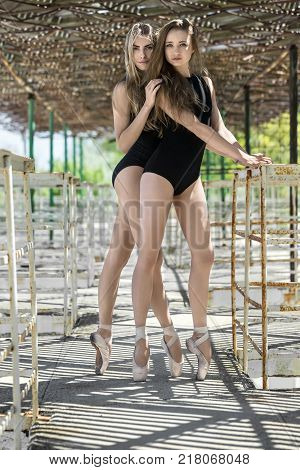 Joyful ballerinas in black leotards stand on the pointes on the concrete pier with metal handrails. They looks into the camera with parted lips and a smile. Sunlight creates stripe shadows. Outdoors.
