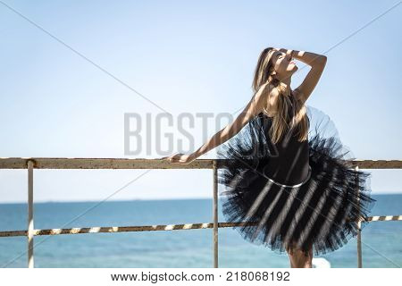 Sensual ballerina with closed eyes and parted lips stands on the background of the sea. She wears a black leotard with a tutu. Sunlight creates stripe shadows on her. Outdoors. Horizontal.