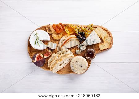 Cheese plate with blue cheese brie truffle hard cheese with grapes figs pears honey crackers dried fruits and nuts on white table. Top view. Copy space.