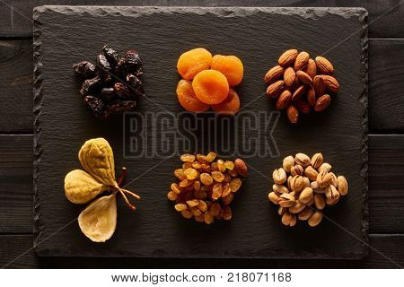 Dried fruits and nuts on slate plate over vintage rustic wooden background
