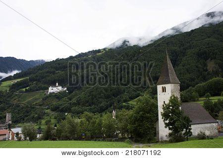 San nicolo church in Burgusio or Burgeis village and Marienberg Abbey or Abtei Marienberg or Abbazia Monte Maria on mountain at Malles Venosta, in val Venosta, in Trentino-Alto Adige, Italy