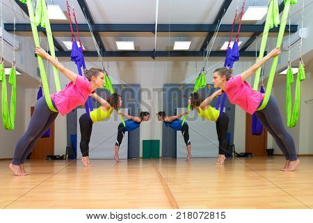 Three pretty girls practice anti-gravity yoga position in gym on hammocks - doing exercises meditating in calm position on a aerial yoga class in front of a mirror .