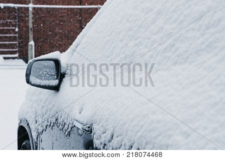 Side mirror on a car covered in snow, selective focus