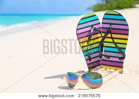 Multicolored flip-flops and sunglasses on a sunny beach of Seychelles