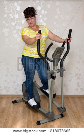 young plump woman exercising on trainer ellipsoid