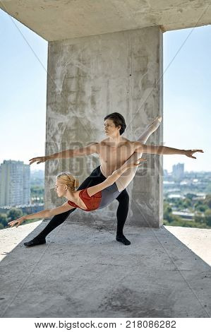 Wonderful couple of ballet dancers posing on the concrete floor of the unfinished building on the cityscape background. Topless guy wears a black dance pants, girl wears a red-gray leotard. Vertical.