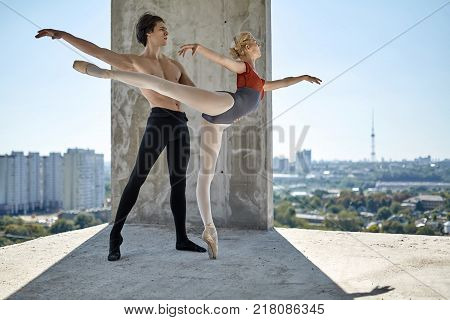 Nice couple of ballet dancers posing on the concrete floor of the unfinished building on the cityscape background. Topless guy wears a black dance pants, girl wears a red-gray leotard. Horizontal.