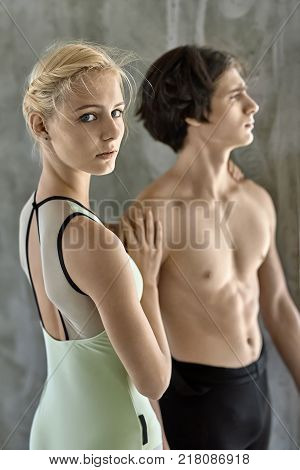 Tender couple of ballet dancers posing on the concrete wall background. Topless guy wears a black dance pants and looks forward. Girl wears a green leotard and looks into the camera with parted lips.