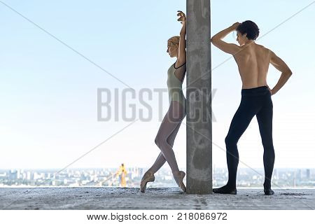 Athletic couple of ballet dancers lean on the concrete wall on the floor of the unfinished building on the cityscape background. Topless guy wears a black dance pants, girl wears a green leotard.