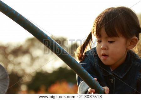 Japanese Girl Playing In The Park At Evening (3 Years Old)