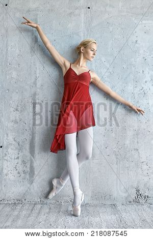 Tender ballerina leans on the concrete wall with outstretched to the sides arms. She wears a red skirted leotard with light leggings and pointe shoes. Girl looks to the side. Sun shines onto her body.