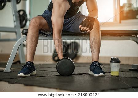 Muscular man at gym taking a break from workout sitting side mineral salt.Body and mind workout in l