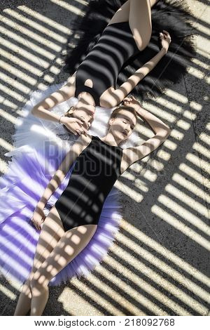 Pretty ballerinas with closed eyes lying on the multicolored tutus on the concrete floor outdoors. They wear black leotards. Sunlight creates stripe shadows on them. Top view photo. Vertical.