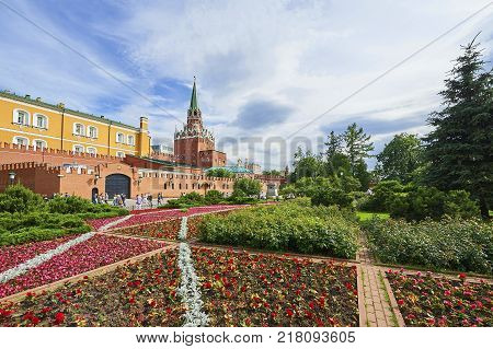 MOSCOW, JUN. 29, 2017: View on Moscow Kremlin Red Square Alexander garden flowers flower beds and walking people, tourists. Moscow tours vacations holidays. City garden park colorful flowers and trees