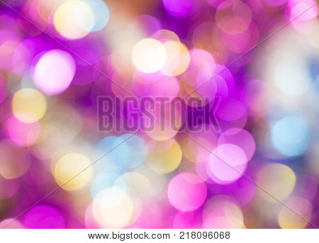 Beautiful out of focus vivid round lights background of changing slowly violet blue orange yellow pink and purple colors